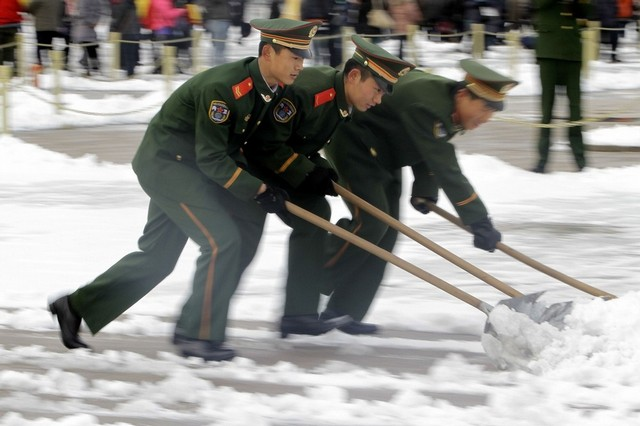 Paramilitary policemen shovel snow at Tiananmen Square in Beijing