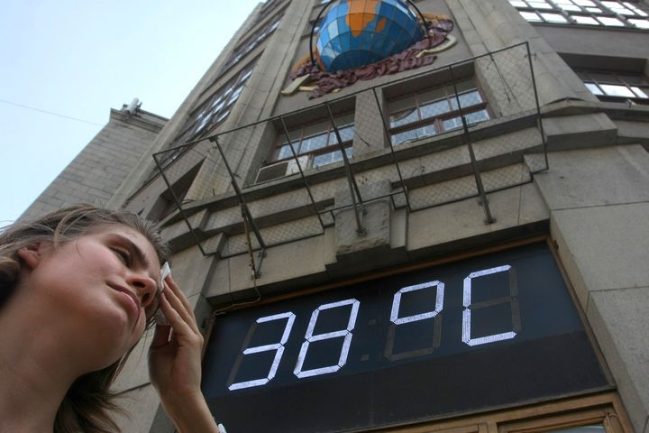 A Russian girl wipes her forehead while standing near a temperatre sign reading 38 degress celsius, 100 fahrenheit, in Moscow on July 29, 2010. Muscovites coughed their way through the hottest days of weather on record in the Russian capital as a smog cloud created by peat fires blanketed the city.  AFP PHOTO / ANDREY SMIRNOV