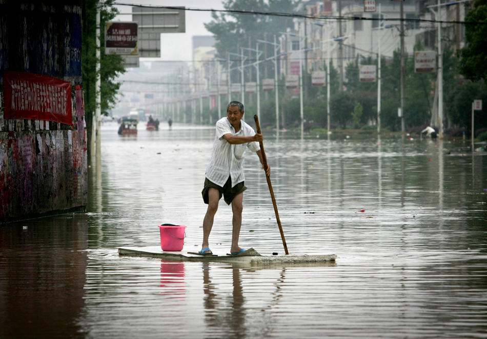 A Chinese man rows a makeshift raft in a flooded street in Xianing city in central China's Hubei province on Wednesday, June 15, 2011. More heavy downpours are forecast this week over central and southern China, where seasonal flooding has already killed more than 100 people, Chinese state media reported on Monday. (AP Photo)