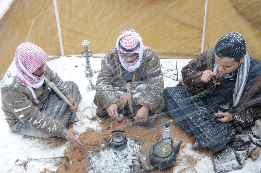 Saudi men drink tea as they sit in a tent during a snowstorm in Alkan village, west of Saudi Arabia December 13, 2013. REUTERS/Mohamed Alhwaity (SAUDI ARABIA - Tags: ENVIRONMENT SOCIETY TPX IMAGES OF THE DAY) - RTX16H72